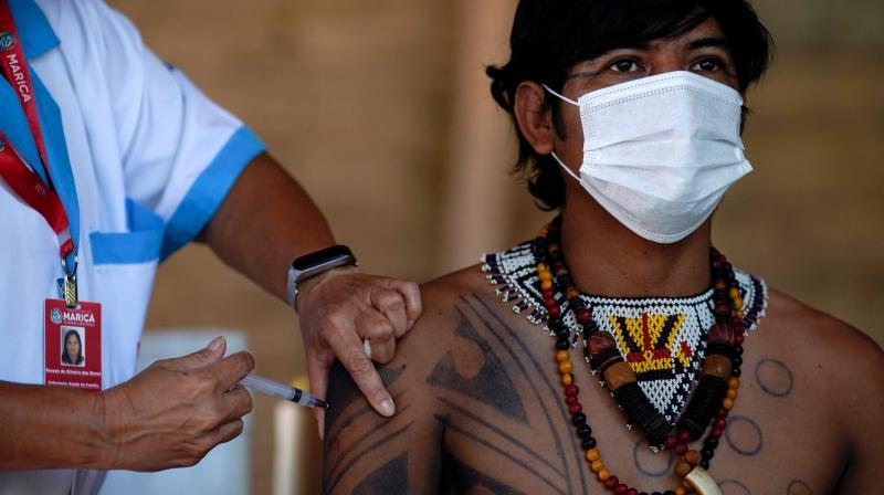 A Guarani indigenous man is inoculated with the Sinovac Biotech's CoronaVac vaccine against COVID-19 at the Sao Mata Verde Bonita tribe camp, in Guarani indigenous land, in the city of Marica, Rio de Janeiro, Brazil, on January 20, 2021, amid the new coronavirus pandemic. (Mauro Pimentel / AFP)