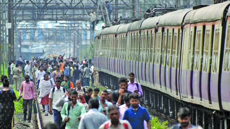 Commuters walk on railway tracks after the overhead wire broke down between Vitthalwadi and Kalyan  railway station on Wednesday. (Photo: DEBASISH DEY)