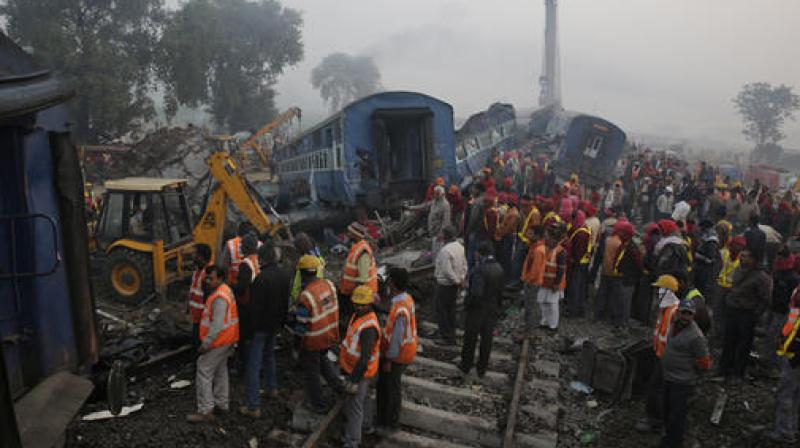 Rescuers work at the site after 14 coaches of an overnight passenger train rolled off the track near Pukhrayan village of Kanpur Dehat district in Uttar Pradesh. (Photo: AP)