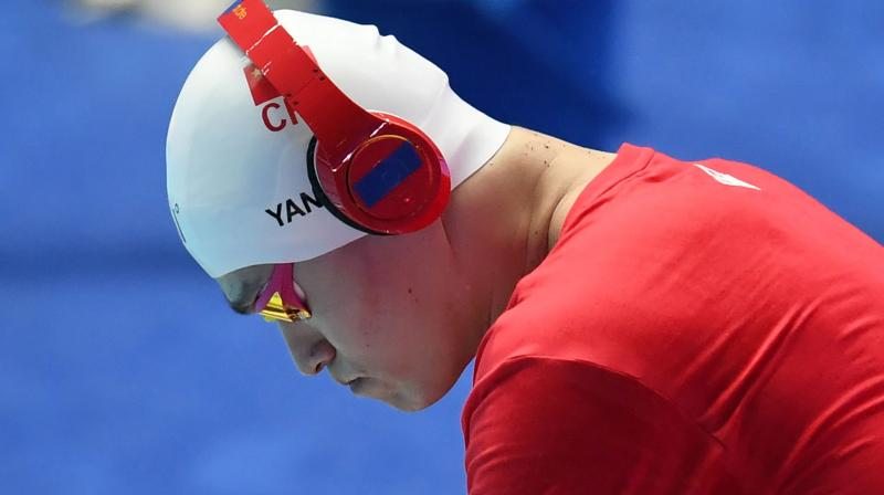 In this file photo taken on July 23, 2019, China's Sun Yang wears headphones prior to the final of the men's 200m freestyle event during the swimming competition at the 2019 World Championships at Nambu University Municipal Aquatics Center in Gwangju, South Korea. China's triple Olympic swimming gold medallist Sun Yang has been found guilty of refusing to give a doping sample and banned for eight years in an eagerly-awaited judgement from the Court of Arbitration for Sport (CAS) on February 28, 2020. (AFP)