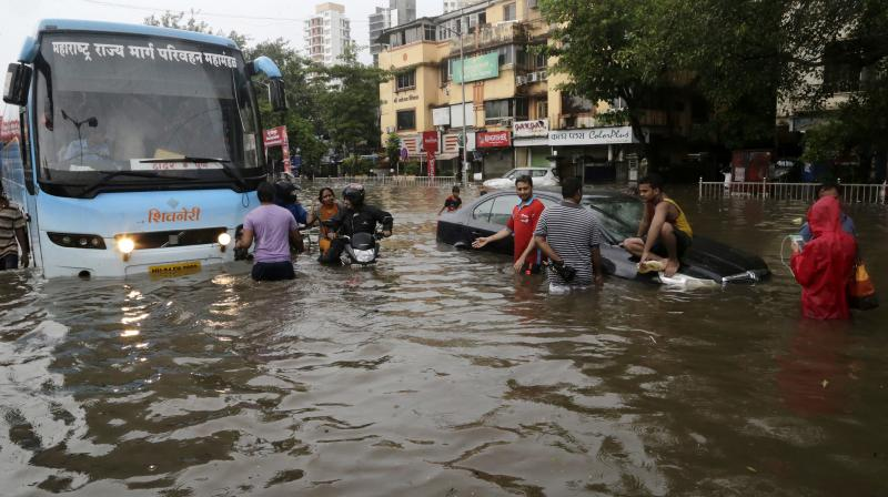 Commuters make their way through a waterlogged street following heavy rains in Mumbai. (Photo: PTI)