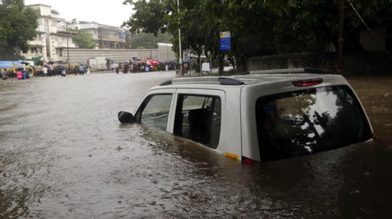 A car seen seen submerged in a flooded street following heavy rains in Mumbai. (Photo: AP)
