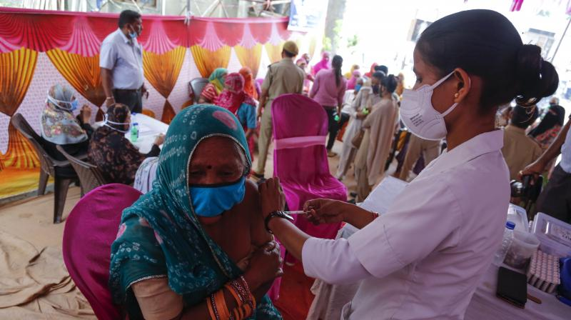 A woman is administered the Covishield vaccine during a vaccination drive against COVID-19 at a mosque in Ahmedabad, India, Monday, June 21, 2021. (AP Photo/Ajit Solanki)