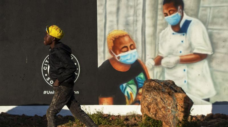 A young boy walks past a mural promoting vaccination for COVID-19 in Duduza township, east of Johannesburg, South Africa. (Photo: AP)