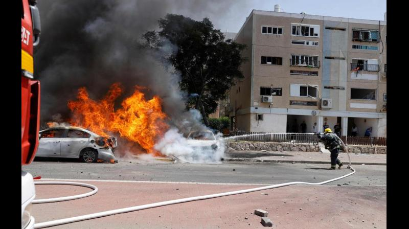 Israeli firefighter extinguishes a burning vehicle on Tuesday after Hamas launched rockets from Gaza Strip to Ashkelon, at southern Israel. (AFP)