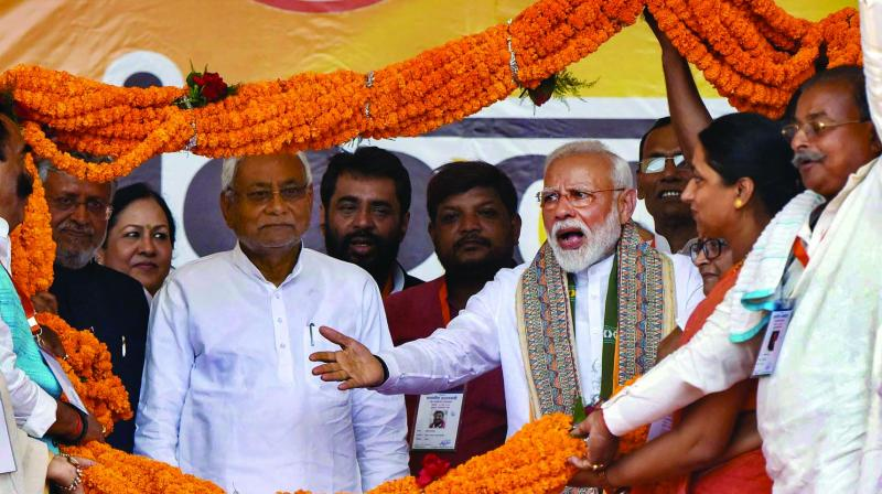 Prime Minister Narendra Modi and Bihar chief minister Nitish Kumar being garlanded during an election campaign rally in Patna on Wednesday. (Photo: PTI)