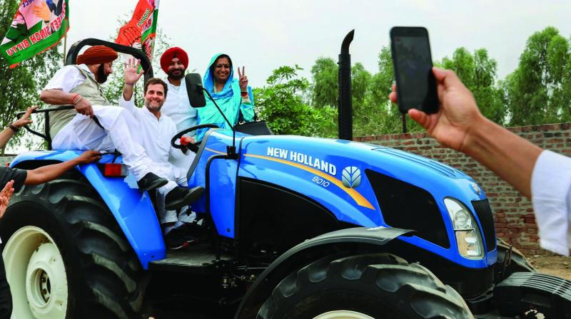 Congress chief Rahul Gandhi waves from the driver's seat of a tractor during a poll campaign in Ludhiana on Wednesday. (Photo: PTI)