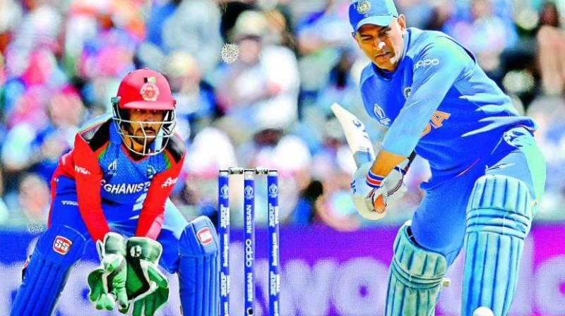 Mahendra Singh Dhoni is watched by Afghanistan's Ikram Ali Khil as he plays a shot during the 2019 Cricket World Cup group stage match between India and Afghanistan in Southampton. (Photo: AFP)