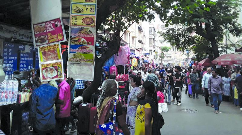 People are seen near food stalls outside a school  premise in Dadar on Sunday. (Photo: SHRIPAD NAIK)
