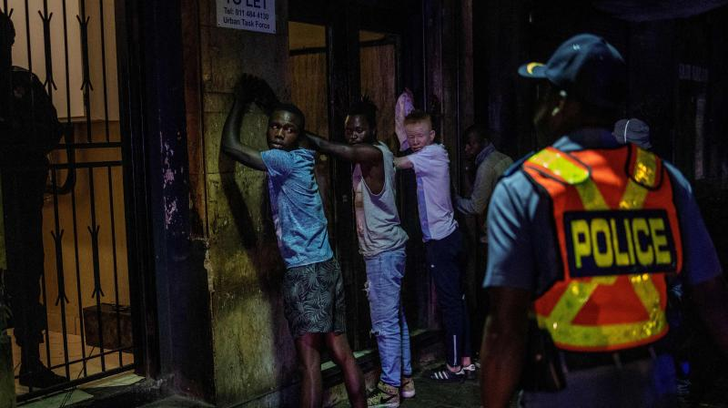Suspects are lined up against a wall as a member of the South African Police Service (SAPS) wearing gloves arrests them because they defied the lockdown order during an operation in the Johannesburg. AFP Photo