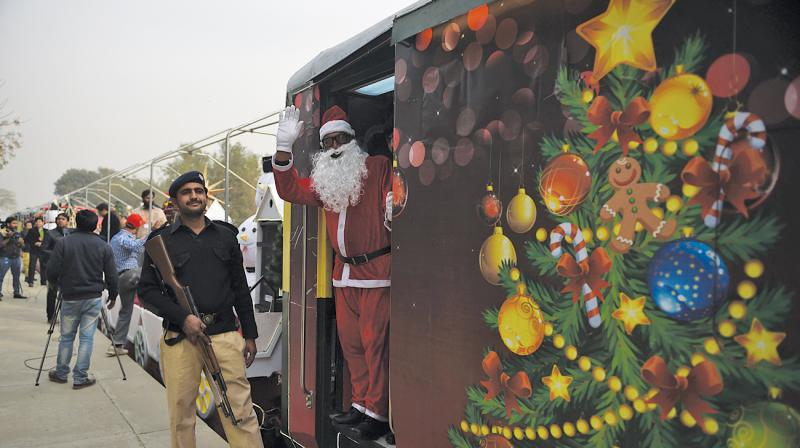 A man dressed as Santa Claus waves from a Christmas-themed train after its inauguration in Islamabad. (Photo: AFP)