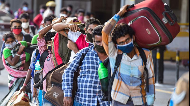 Migrants stand in a queue at Central Railway Station to board a Shramik Special train for West Bengal, during ongoing COVID-19 lockdown, in Chennai. PTI Photo