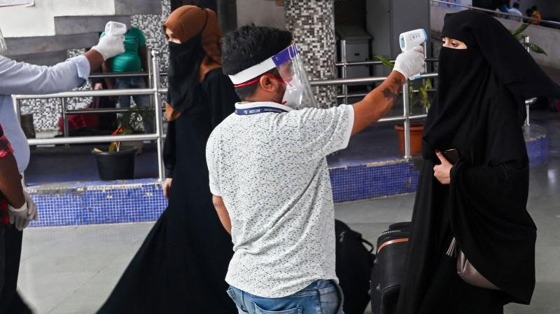 A health worker takes the body temperature of incoming passengers at a railway terminus following restrictions imposed by the state government amidst rising Covid-19 coronavirus cases Mumbai on April 7, 2021. (Indranil Mukherjee / AFP)