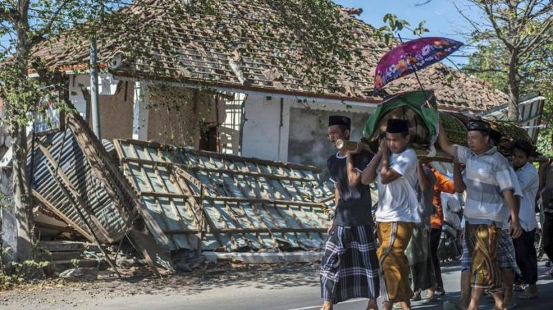 Indonesian men carry the body of a victim of last week's earthquake past a damaged building during a funeral in Gangga, Lombok Island, Indonesia on August 12.(Photo: AP)