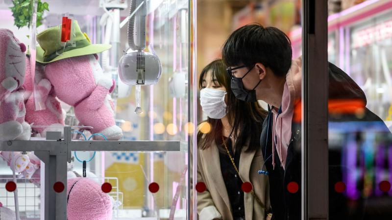 Couple wearing face masks, amid concerns about the spread of COVID-19 in Tokyo (AFP)
