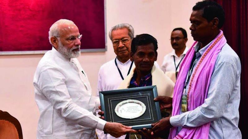 Prime Minister Narendra Modi honouring a descendant of tribal warrior Rendo Majhi.