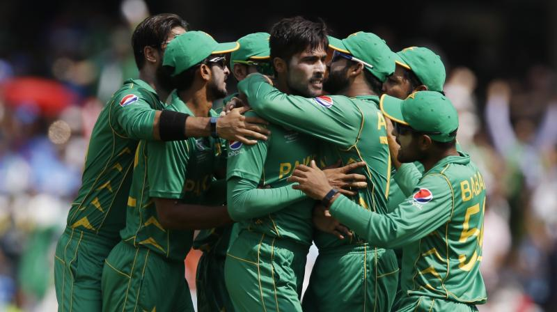 Teammates surround Pakistan bowler Mohammad Amir after he dismissed India's captain Virat Kohli for 5 runs during the ICC Champions Trophy final  (Photo: AP)