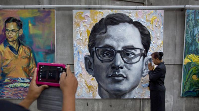 A Thai mourner poses for a photograph while paying tribute in front of a portrait of late Thai King Bhumibol Adulyadej close to the Grand Palace in Bangkok. (Photo: AP)