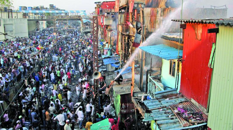 Firefighters attempt to douse the flames at Garibnagar slums as helpless locals, and policemen look on. (Photo: Mrugesh Bandiwadekar)
