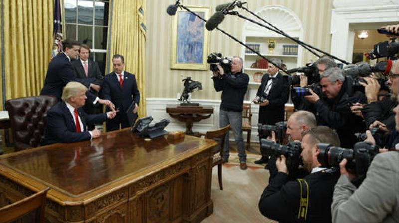 President Donald Trump hands over his pen after signing his first executive order in the Oval Office of the White House in Washington. (Photo: AP)