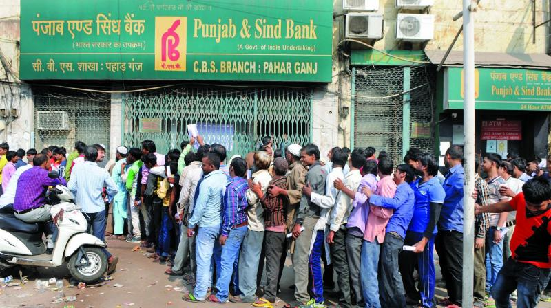 People stand outside a bank to exchange notes in Paharganj. (Photo: Biplab Banerjee)