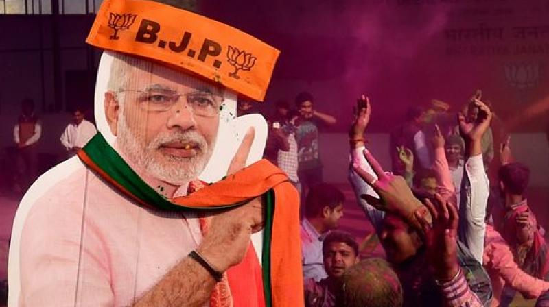 BJP workers play holi with a giant cut-out of Prime Minister Narendra Modi as they celebrate the party's victory in the UP and Uttarakhand Assembly elections, at the party headquarters in New Delhi. (Photo: PTI)
