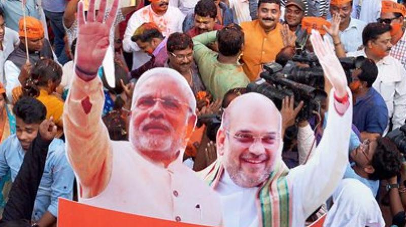 BJP workers carry a cut-out of PM Narendra Modi and BJP President Amit Shah as they celebrate the party's victory. (Photo: File)
