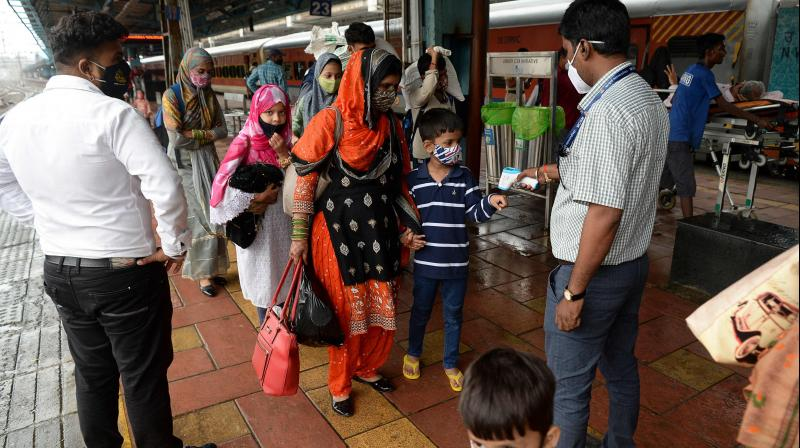 A medical staff checks the body temperature of a young passenger upon his arrival at a railway platform in Mumbai on September 13, 2021. (Indranil MUKHERJEE / AFP)