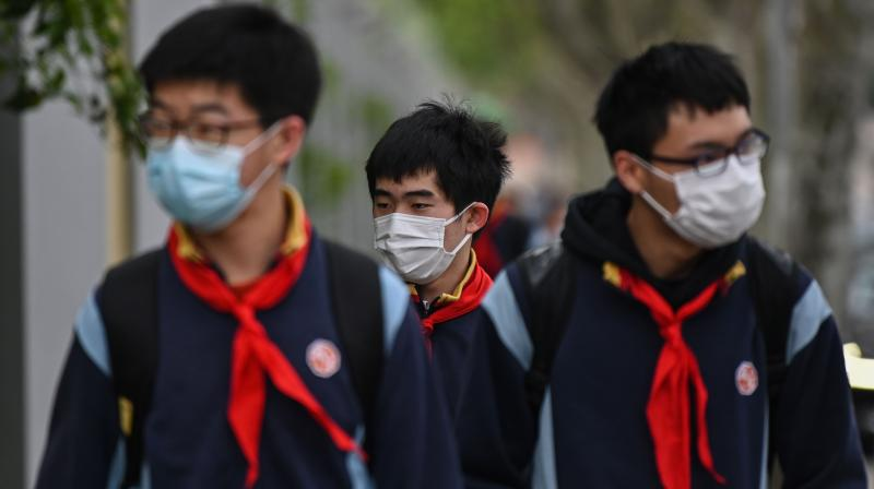 Students wearing face masks arrive at the Huayu Middle School in Shanghai. AFP Photo