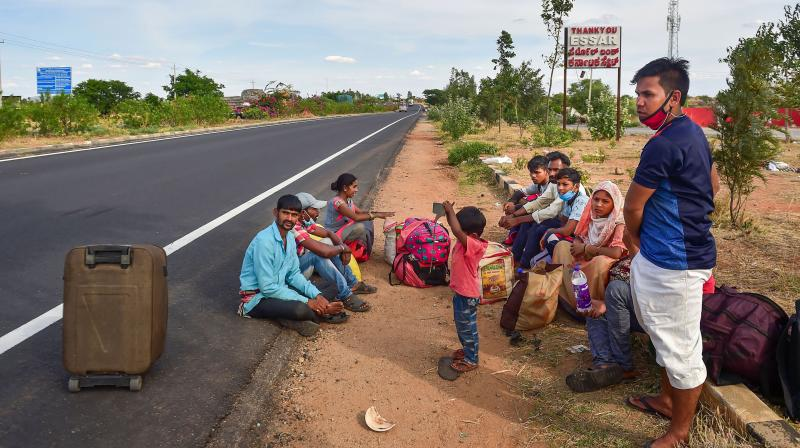 Migrants take rest along the national highway, during their journey towards their native place, amid the ongoing nationwide COVID-19 lockdown, at Devanahalli near Bengaluru. PTI Photo