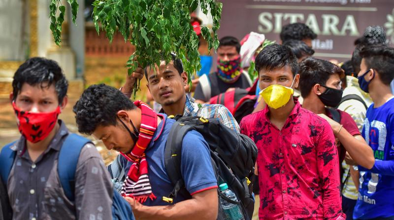 A stranded student from northeast holds a leafy branch to protect himself from scorching heat. PTI Photo