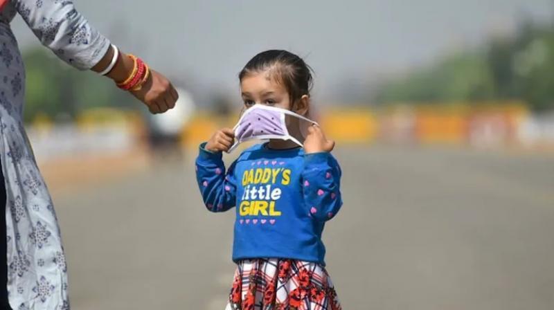 A girl wearing a mask walks near India Gate in New Delhi. (Photo: PTI/File)
