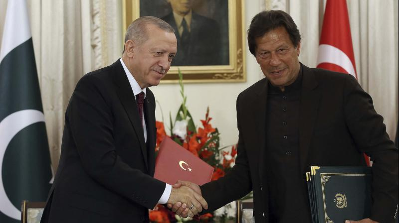 Turkey's President Recep Tayyip Erdogan, left, and Pakistan Prime Minister Imran Khan pose for photos before a meeting, in Islamabad, Pakistan on Friday. PTI photo