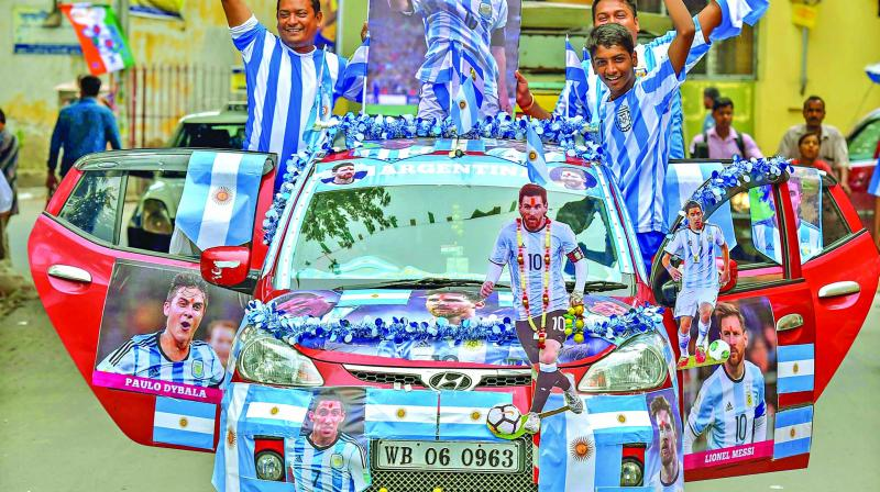 Kolkata youngsters flaunt their loyalty to Argentina by decorating a car with posters of Messi & Co. (Photo: PTI)
