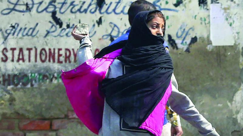 A girl throws a stone towards policemen during a protest in Srinagar, on Tuesday. (Photo: PTI)