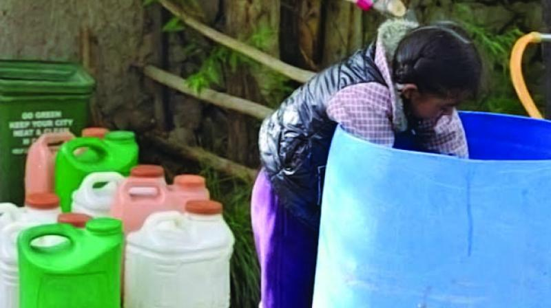 A young girl in Leh struggles to fill her water can (Photo: Padma Ladol)
