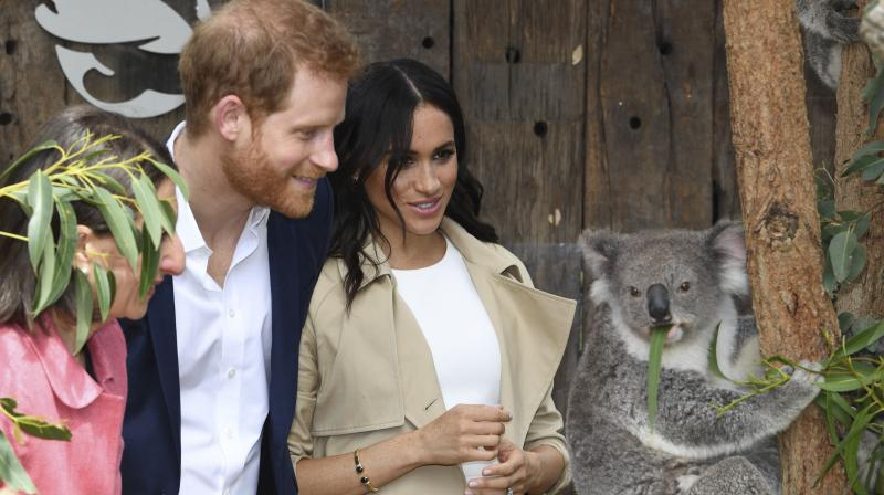 Britain's Prince Harry and his wife Meghan meet a koala named Ruby and its koala joey named Meghan after the Duchess of Sussex during a visit to Taronga Zoo in Sydney on October 16, 2018. (Photo: AFP)