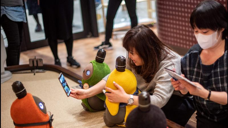 In this picture taken on December 20, 2020 shows diners interacting with robots Lovot in a cafe in Kawasaki. (Philip FONG / AFP)