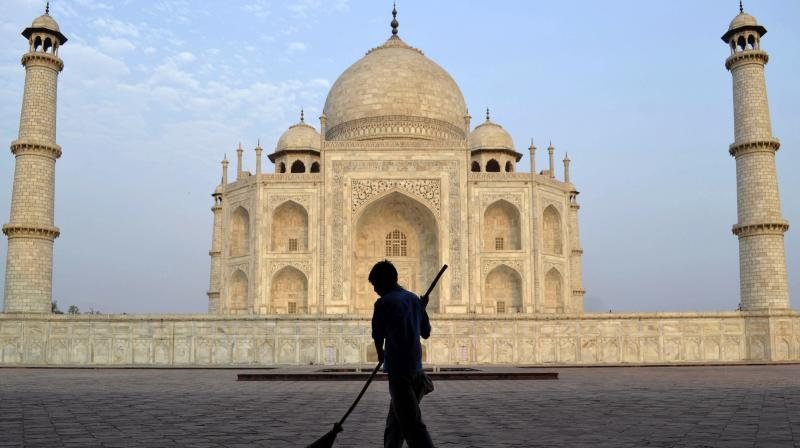 A worker sweeps in front of the Taj Mahal in Agra, India. (Photo: AP)