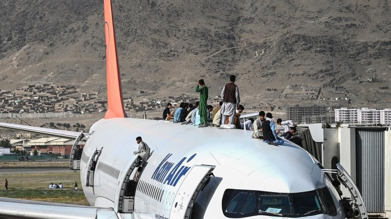 Afghan people climb atop a plane as they wait at the Kabul airport in Kabul. (Representational Photo:AFP)