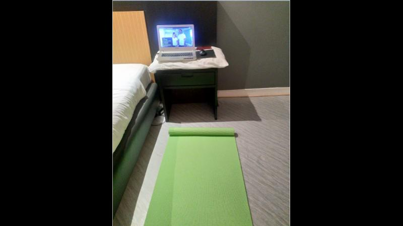 Big bed, laptop, yoga mat — all part of the quarantine experience.