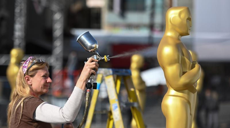 Scenic artist Dena D'Angelo spray paints an Oscar statue gold for the 92nd annual Oscars show set for February 10, 2020 in Hollywood, California. (AFP)
