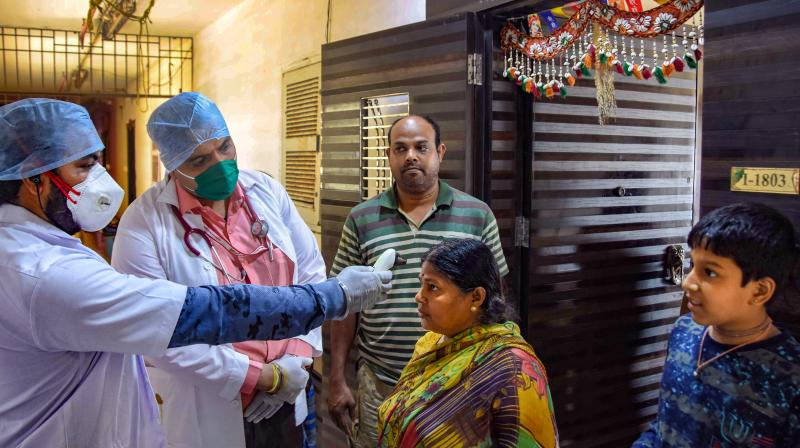 Medics conduct door-to-door thermal screening of residents in Mumbai on March 29, 2020. (PTI)