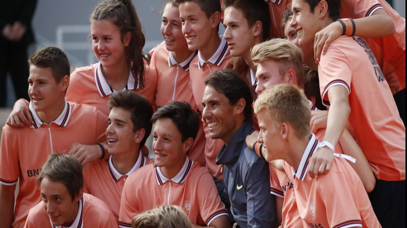 Rafael Nadal poses with ball girls and boys as he celebrates his record 12th French Open title. AP Photo
