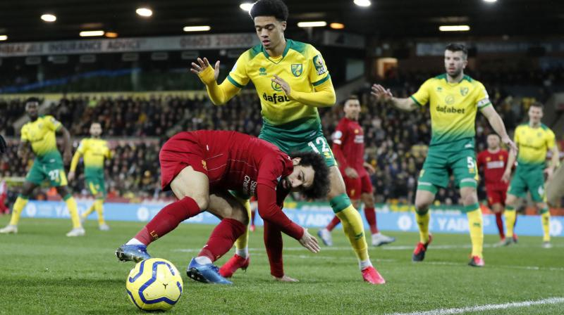Liverpool's Mohamed Salah duels for the ball with Norwich City's Jamal Lewis during their English Premier League match. AP Photo