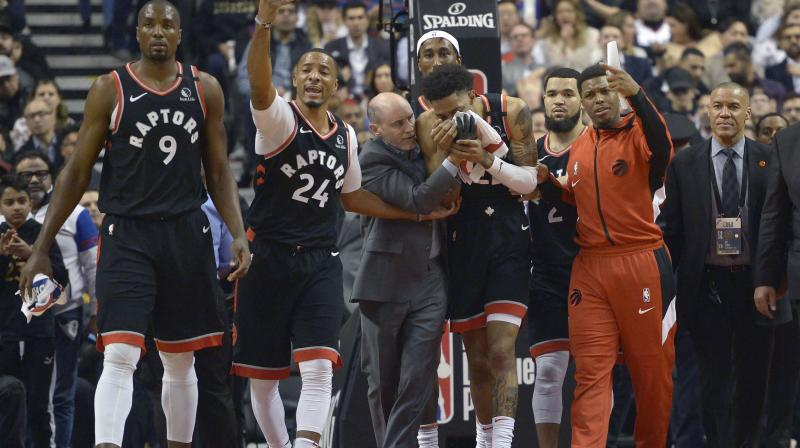 Toronto Raptors guard Patrick McCaw (22) leaves the court with help from players and staff after an injury during their NBA game against the Philadelphia 76ers. AP Photo