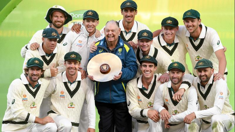 The Australian team celebrates with the trophy after winning the second Test against Pakistan in Adelaide. AFP Photo
