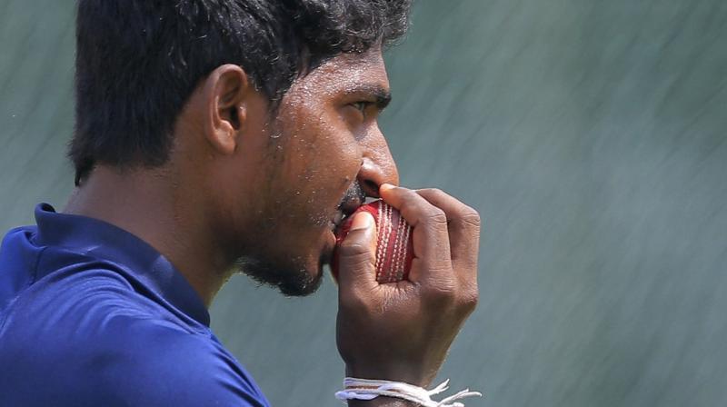 Sri Lanka's bowler Lakshan Sandakan bites the ball during a training session in Colombo, Sri Lanka. AP Photo