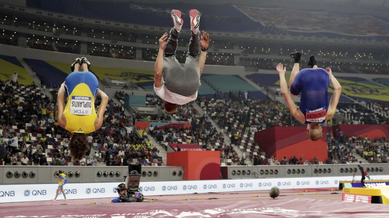 Armand Duplantis of Sweden (L), Piotr Lisek of Poland (C) and Sam Kendricks of the United States do flips after the the men's pole vault final at the World Athletics Championships in Doha, Qatar. AP Photo