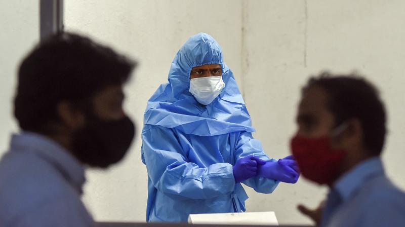A medic wearing protective gear gestures during medical screening of residents for COVID-19, at Dadar in Mumbai. PTI photo